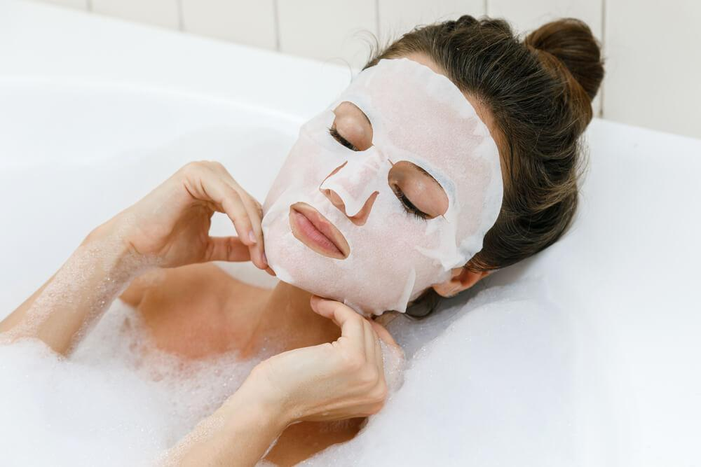 woman applying sheet mask in bath