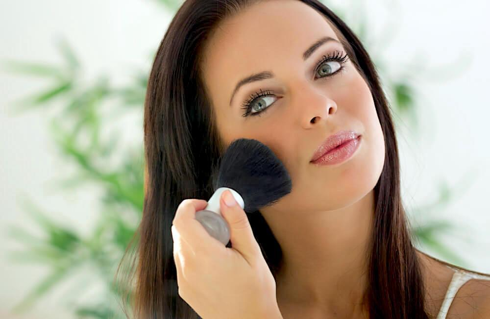 Woman applying blush to cheeks