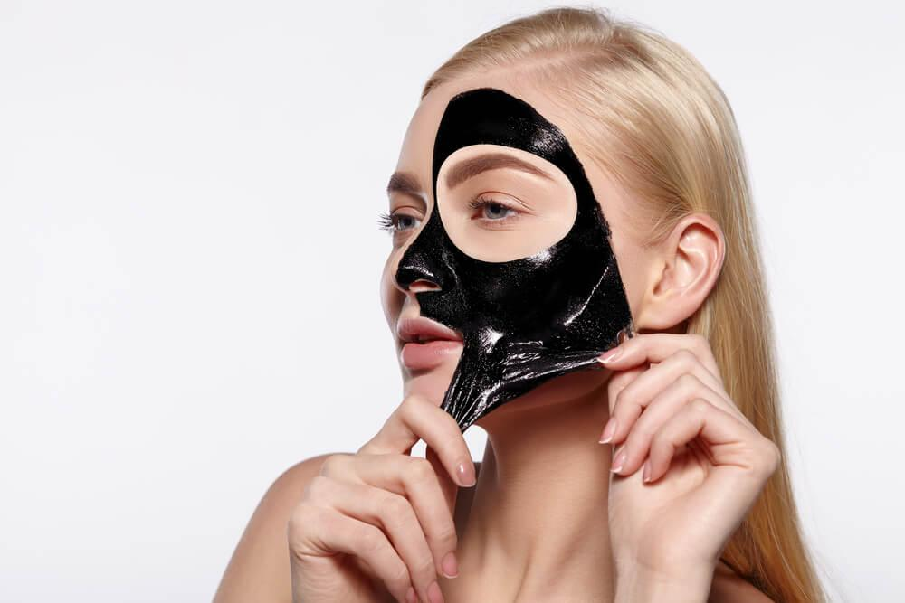 Young woman applying peel-off mask