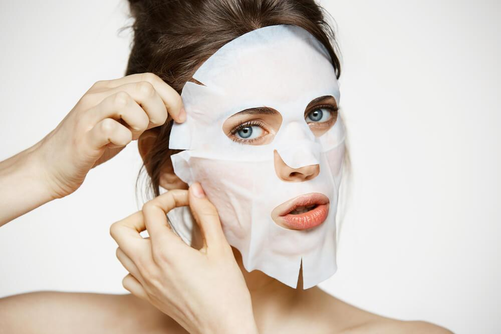 Young woman applying sheet mask to face