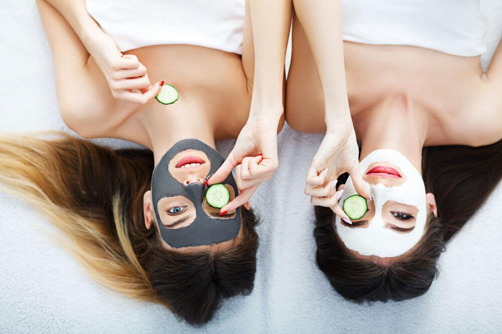 Two young woman with face masks and cucumber slices on eyes