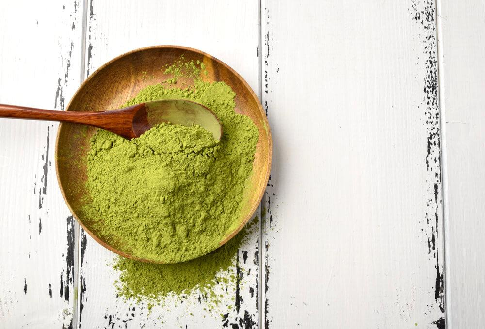 Matcha powder in a wooden bowl with spoon