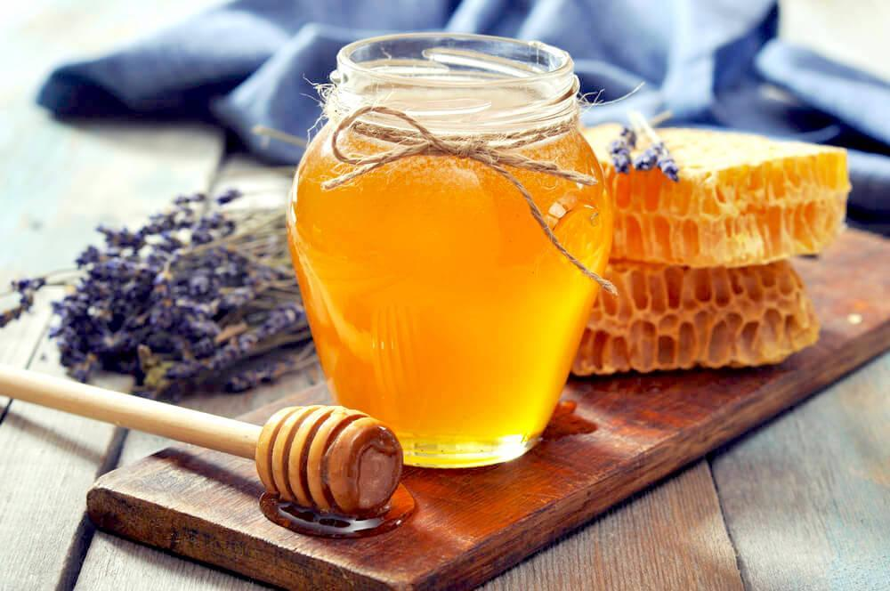 Jar of raw honey with honeycomb behind it