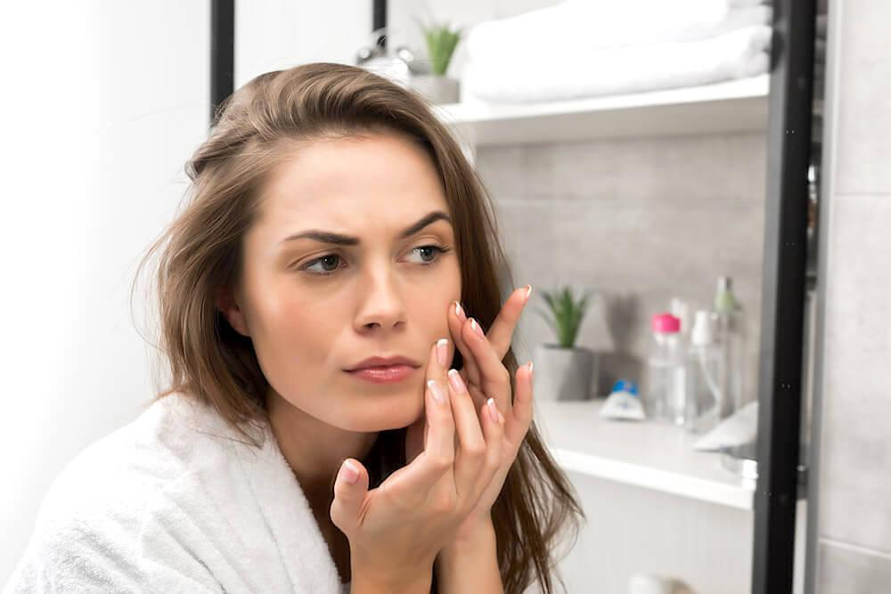 Young woman checking her skin for pimples