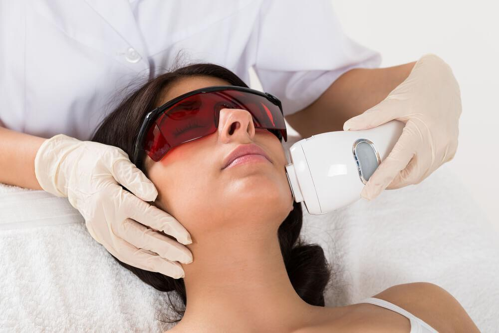 Woman wearing goggles while undergoing laser skin treatment