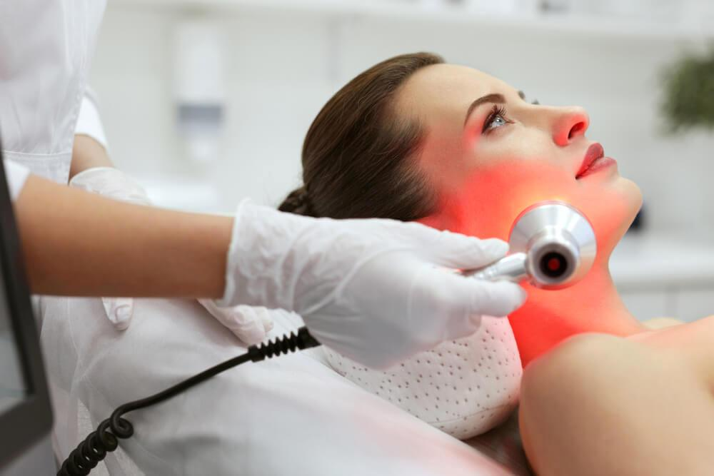 Woman undergoing LED red light therapy on face