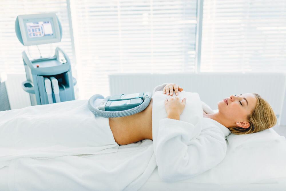 Woman undergoing body sculpting and fat reduction treatment