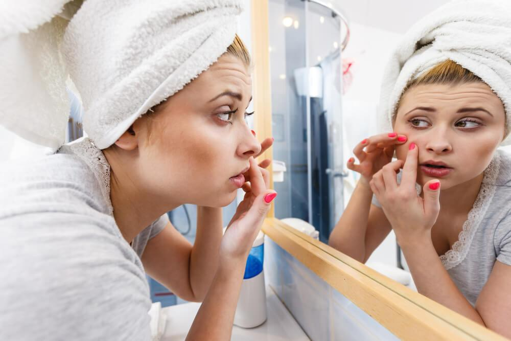 Young woman squeezing pimple in front of mirror
