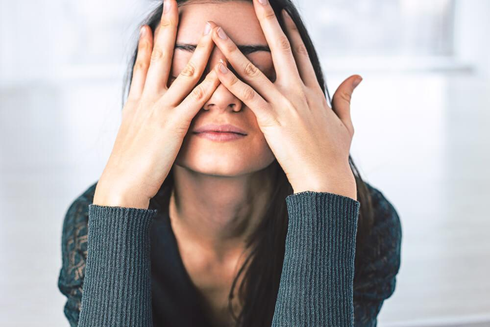 Stressed woman covering her face with her hands
