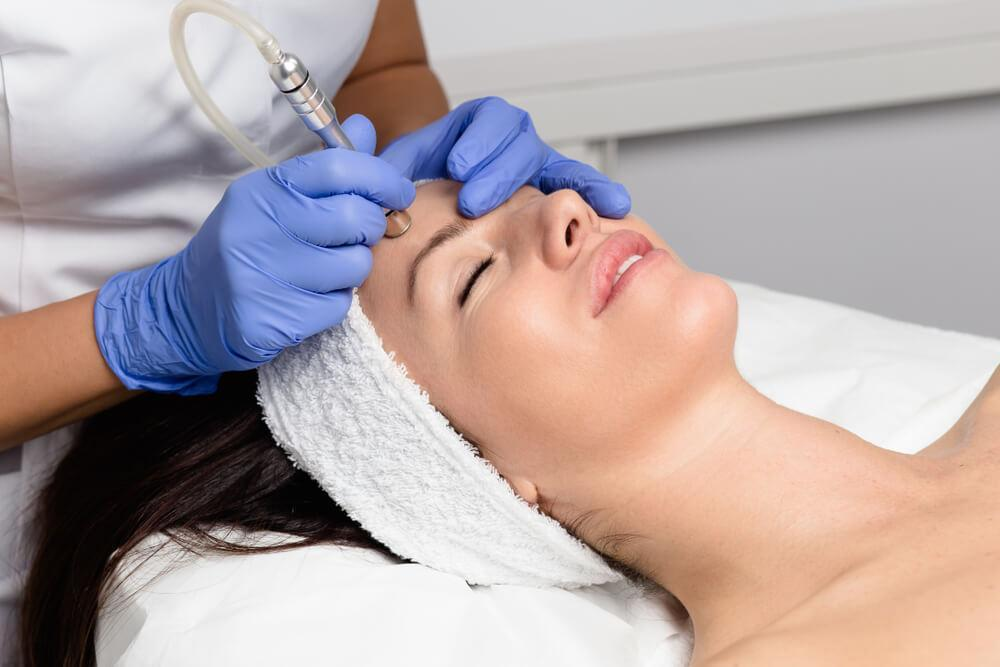 Woman undergoing microdermabrasion treatment