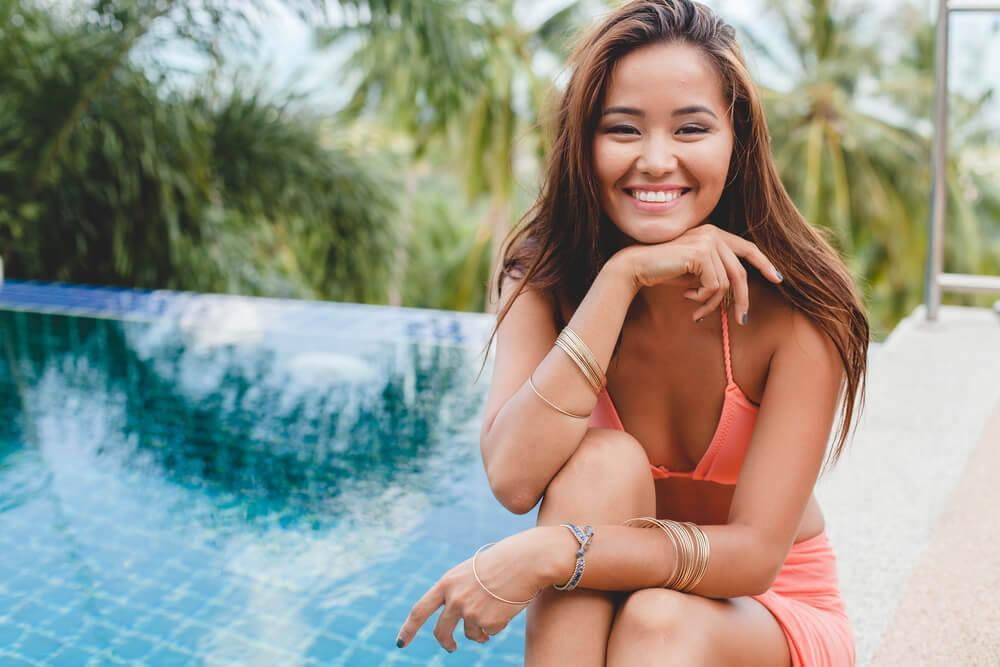 Smiling tanned woman by the pool