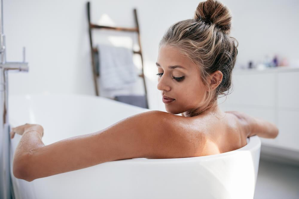 Woman looking at her shoulder in the bath tub