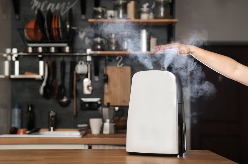 A hand over the steam from a humidifier