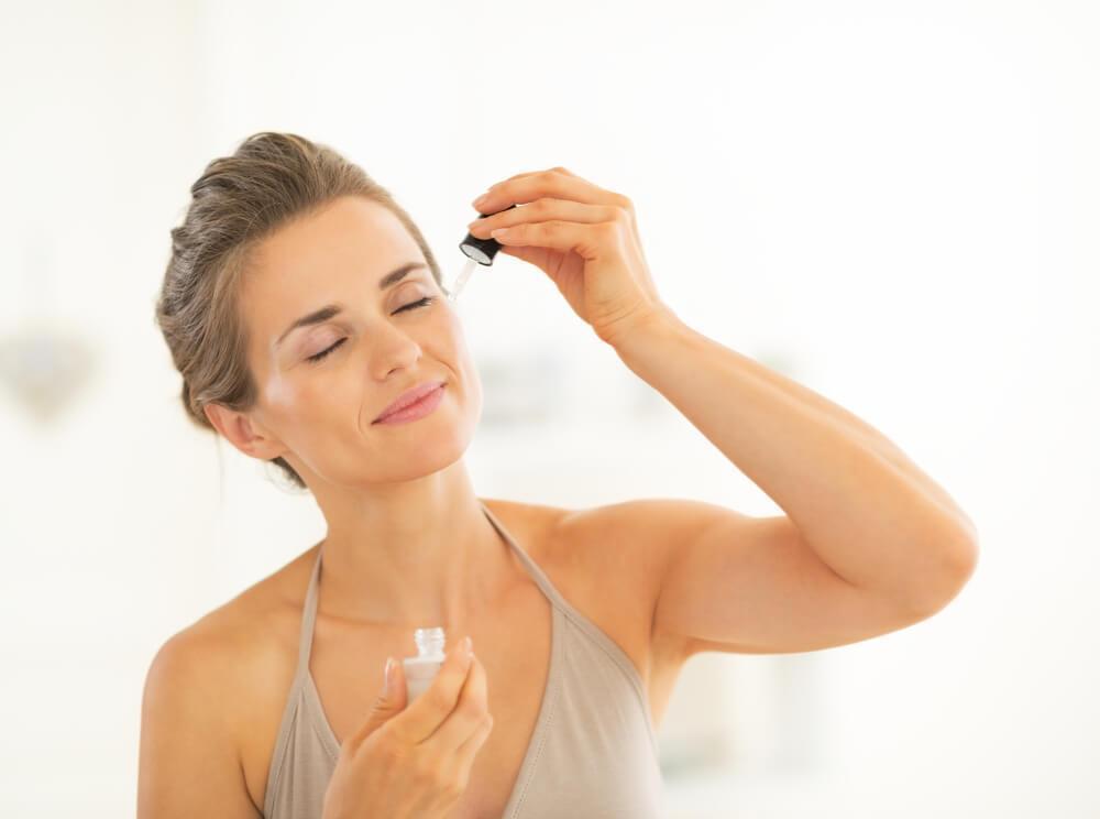 Woman applying serum to face