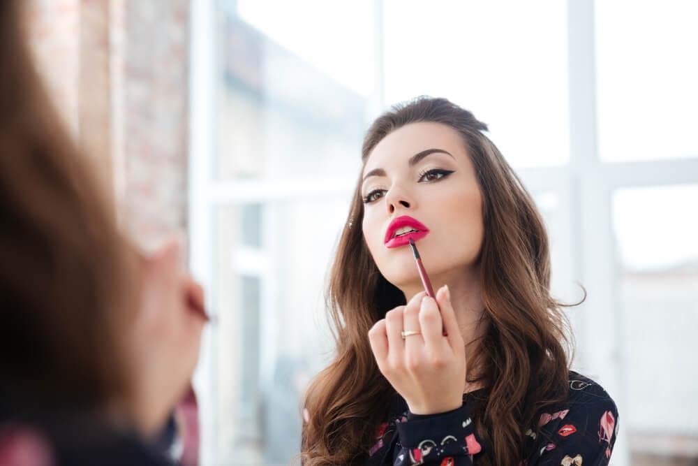 Woman applying red lip gloss