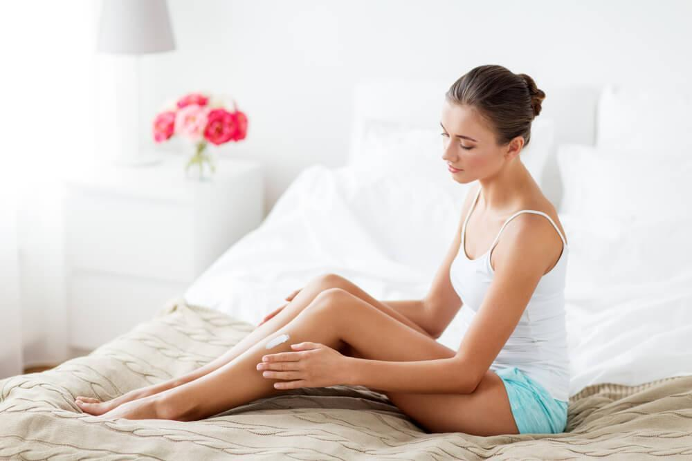 Woman applying self tanning cream to legs on bed