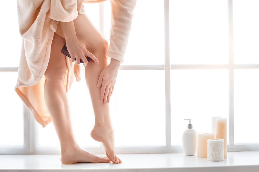 Woman applying self tanning product to leg in bathroom