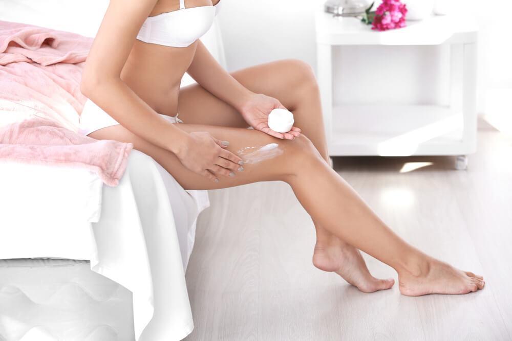 Woman in bedroom applying cream to legs