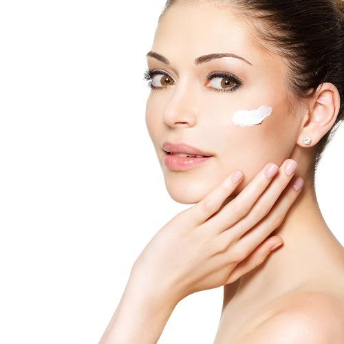 Woman putting skin care cream on her face