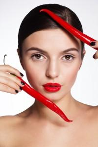 Woman holding cayenne peppers up to her face