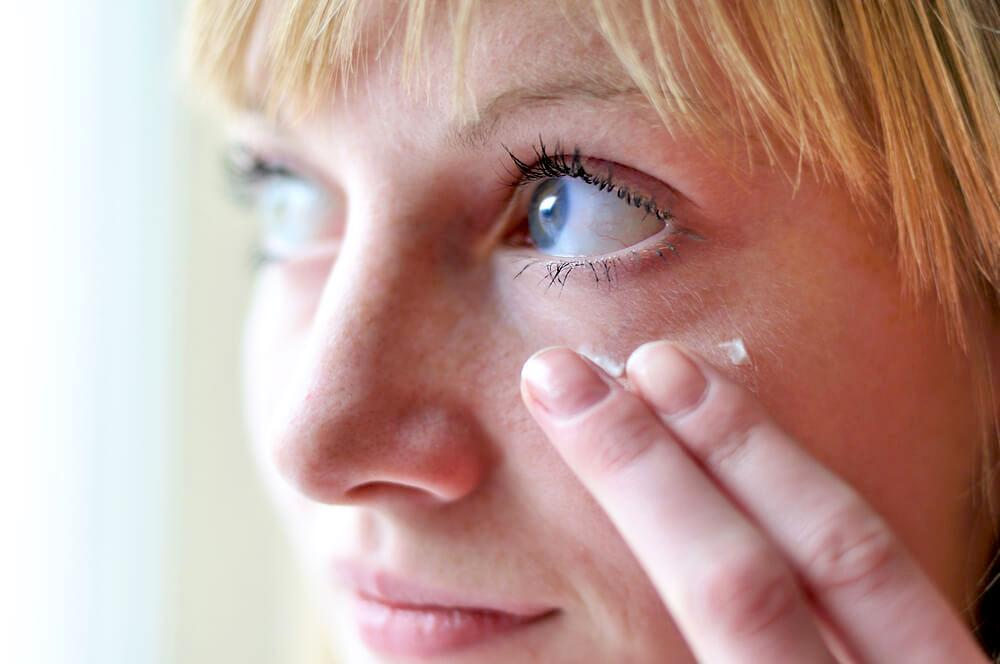 woman applying cream to under eye circle