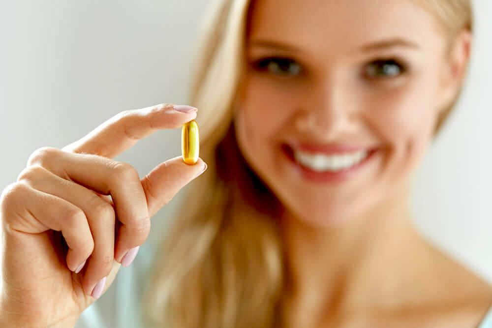 woman holding up a vitamin