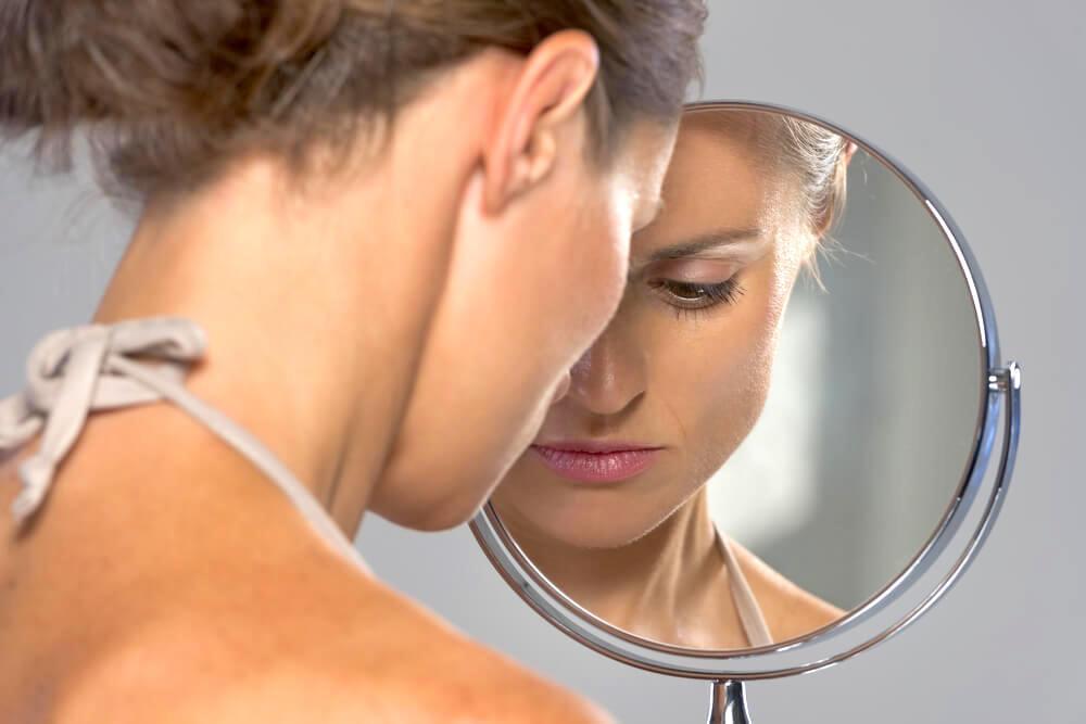 Unhappy woman looking in mirror