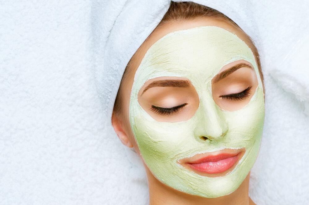 Young attractive woman with pale green clay mask on face