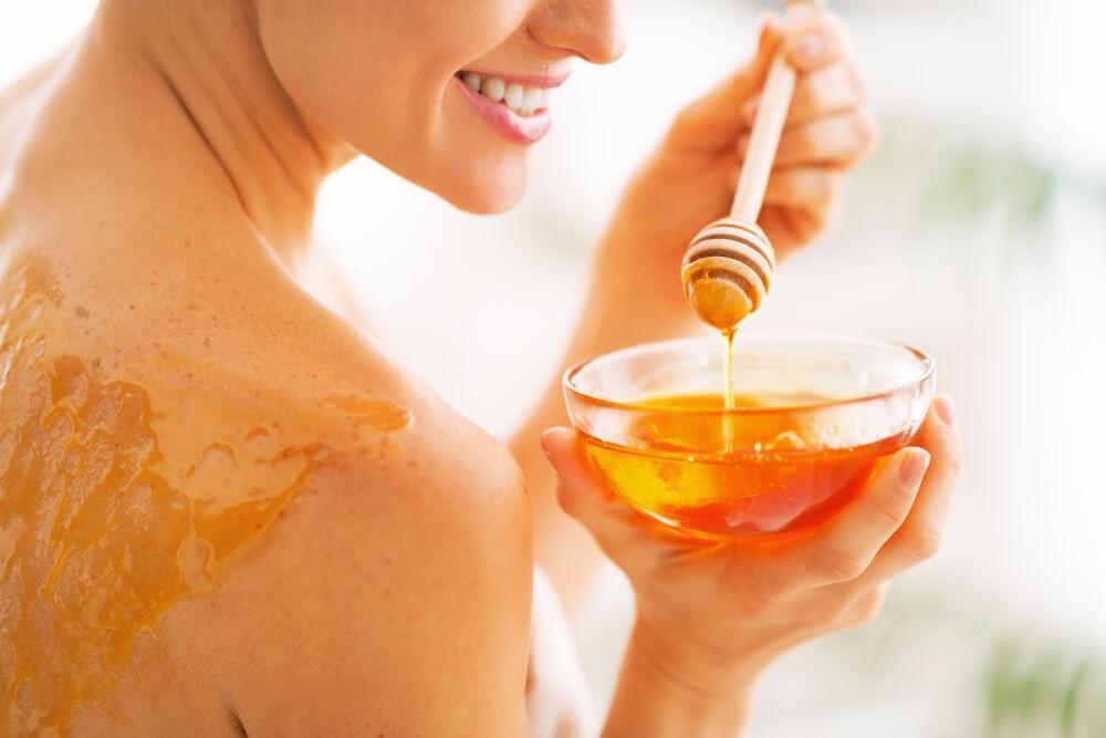 Woman applying honey to skin