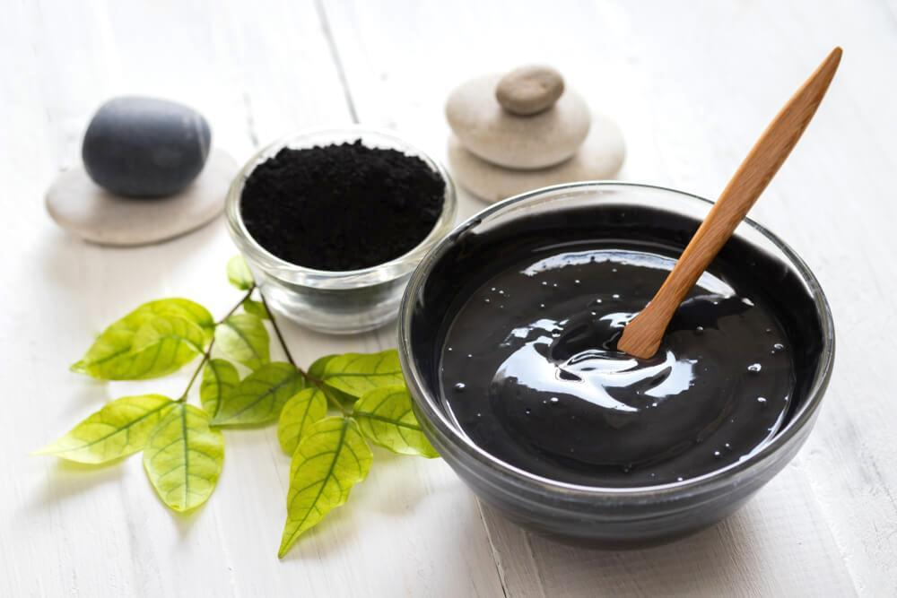 Homemade charcoal mask and ingredients on white table
