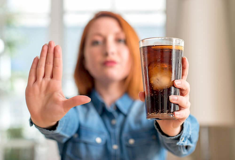 Young woman putting her hand up to say no to a glass of soda