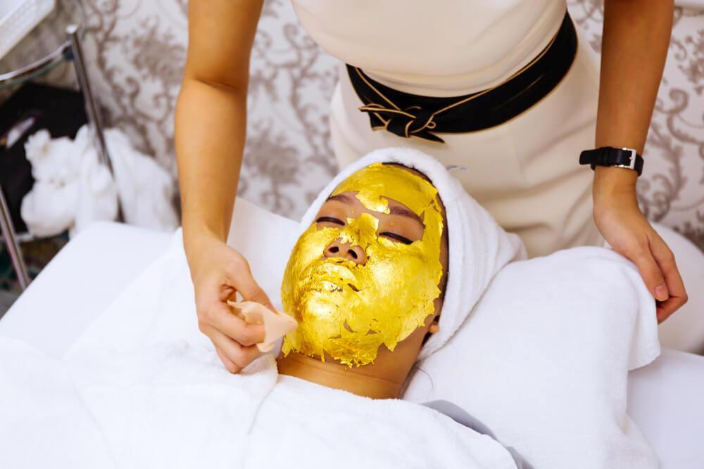 Beautician applying gold leaf face mask to woman's skin