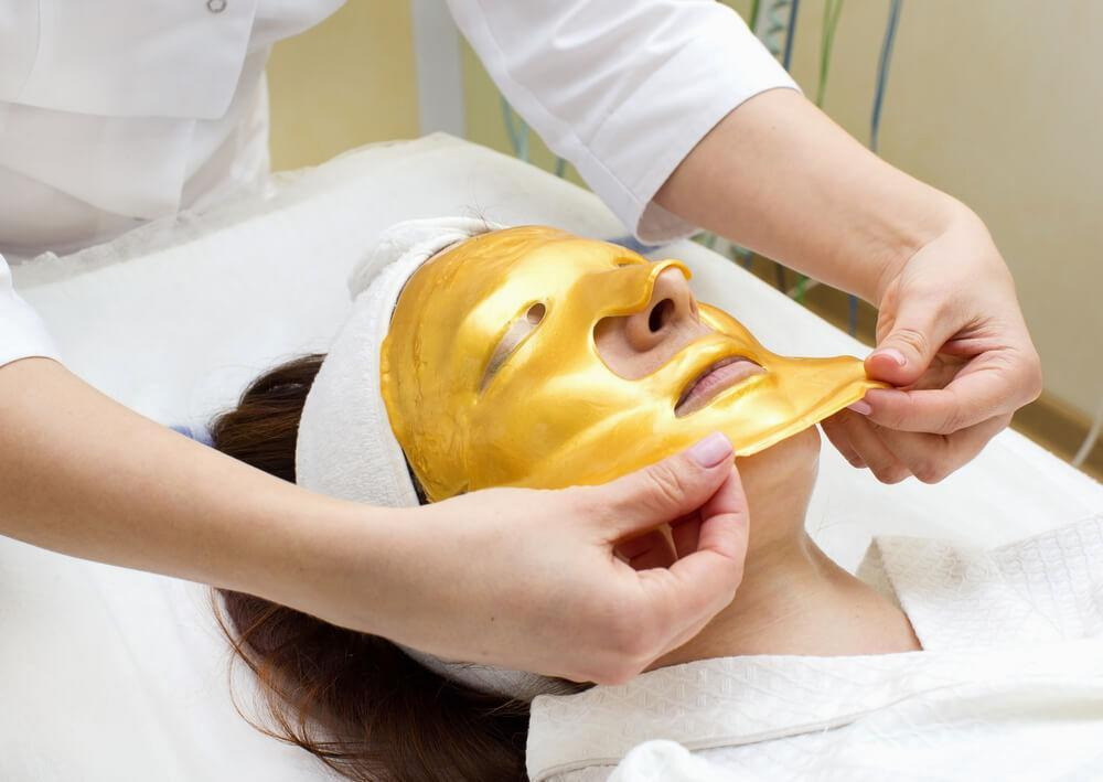 Beautician applying gold mask on woman's skin