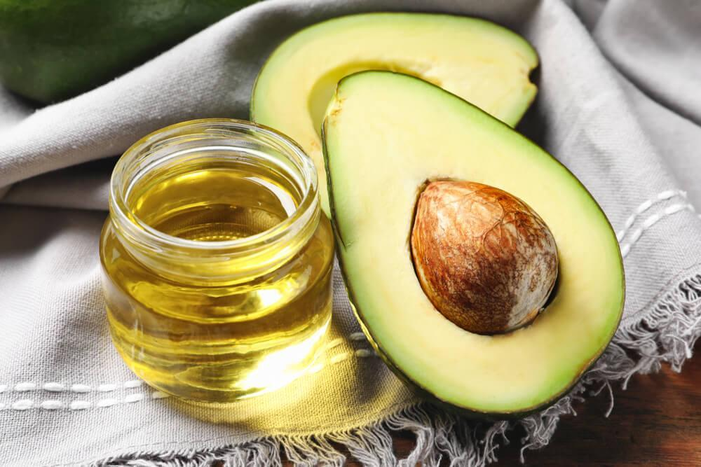 Halved avocado and oil in a small jar
