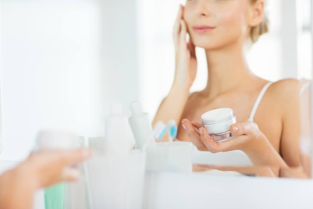 Unknown woman applying moisturiser