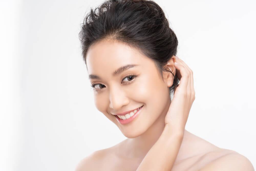 Beautiful smiling woman tucking hair behind ear