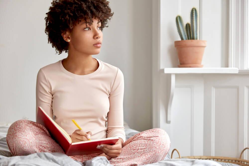 Pensive woman writing in journal