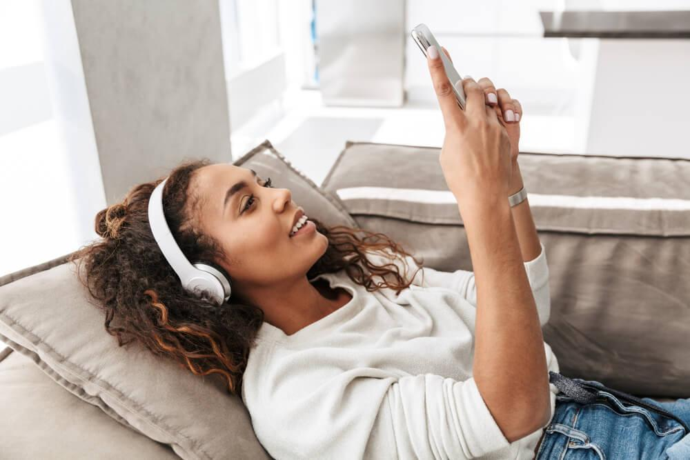Smiling happy woman lying on sofa listening to music and using her phone