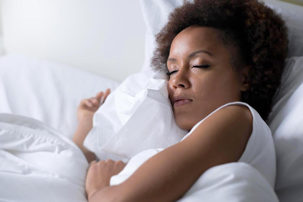 Woman peacefully sleeping and hugging pillow