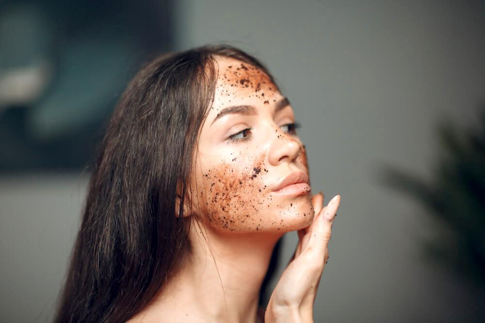 Woman exfoliating face with physical exfoliant beads