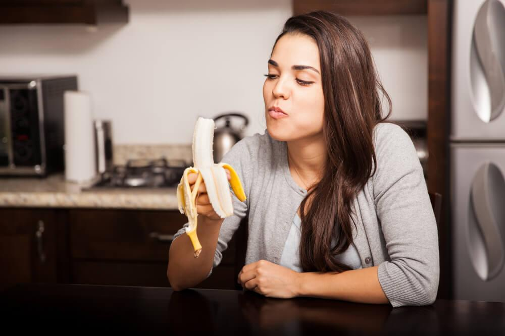 Woman in kitchen eating banana