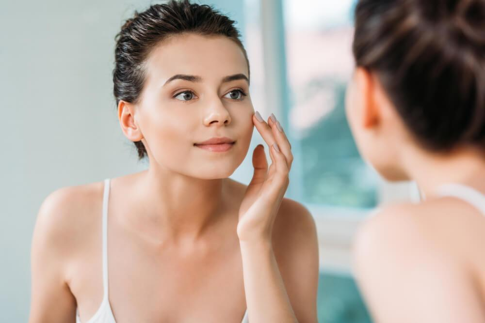 Woman touching face in front of mirror