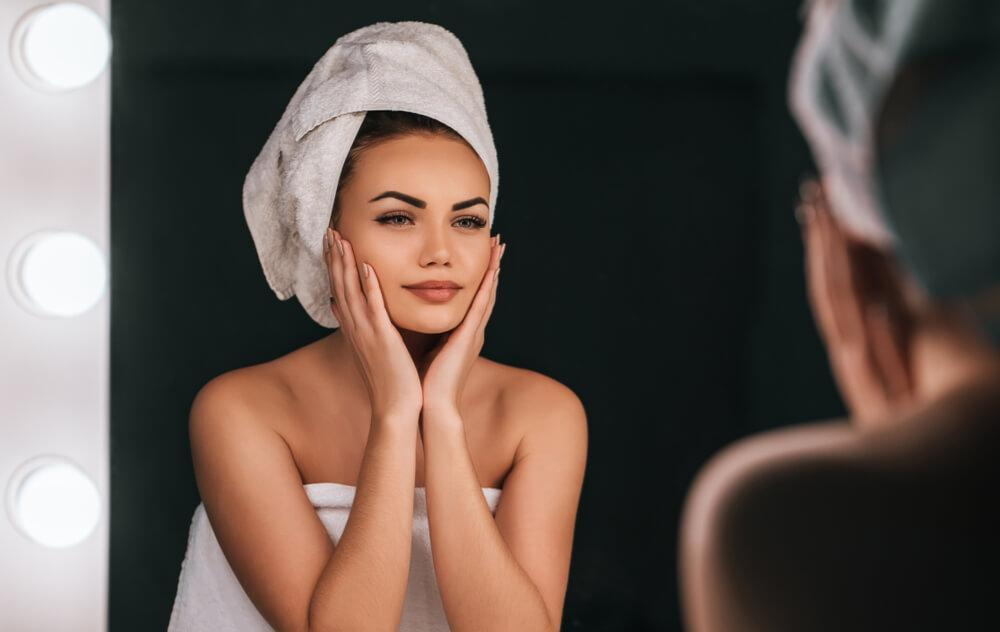 Woman looking at face in mirror with towel on head