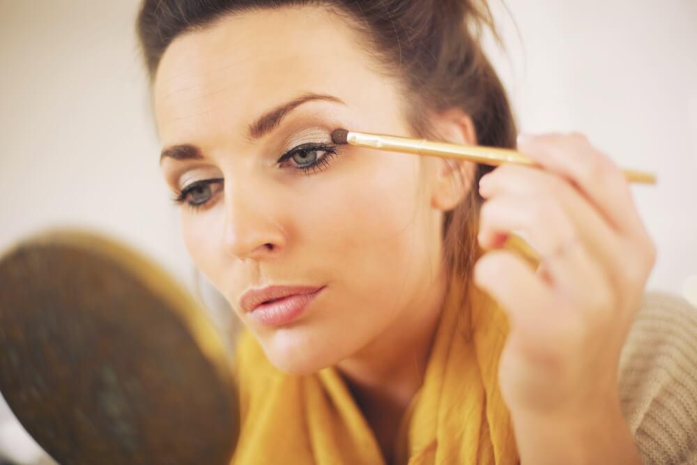 Woman applying eyeshadow with a brush