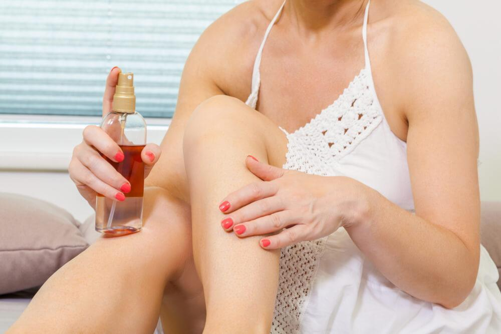 Woman applying self-tanning product to legs