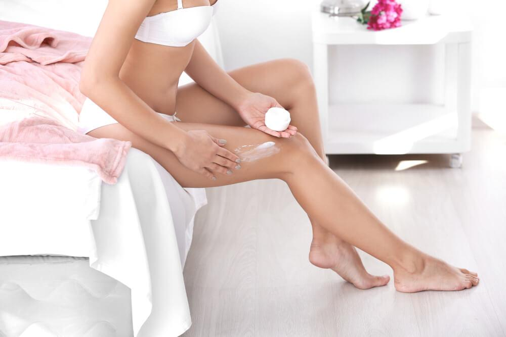 Woman in bedroom applying cream to legs
