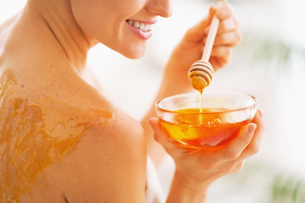 Woman applying honey to her back
