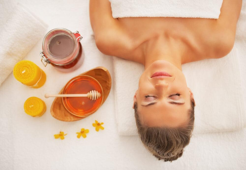 Woman lying down in spa with honey next to her