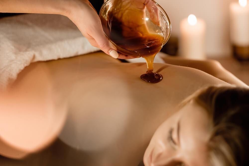 Spa treatment with honey pouring on woman's back