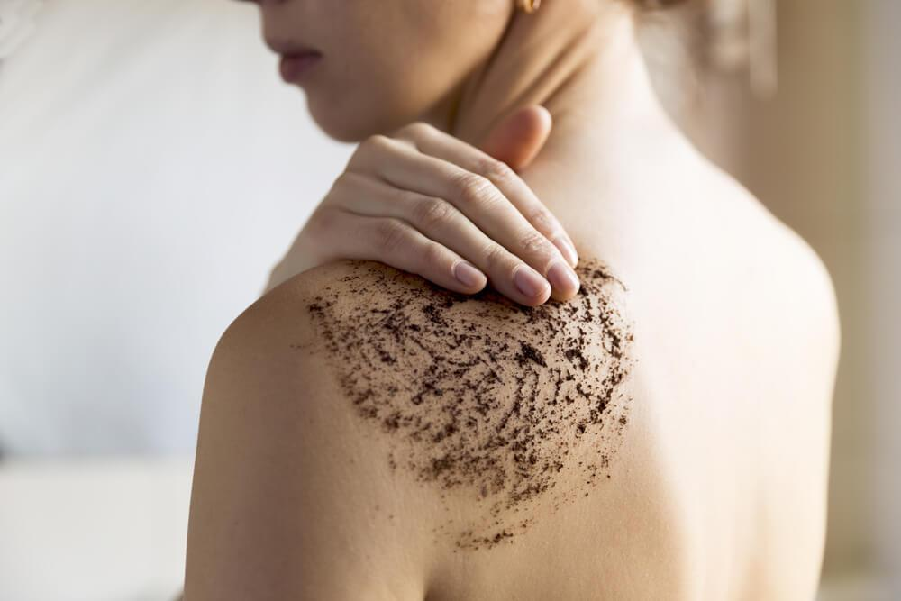 Woman using coffee scrub